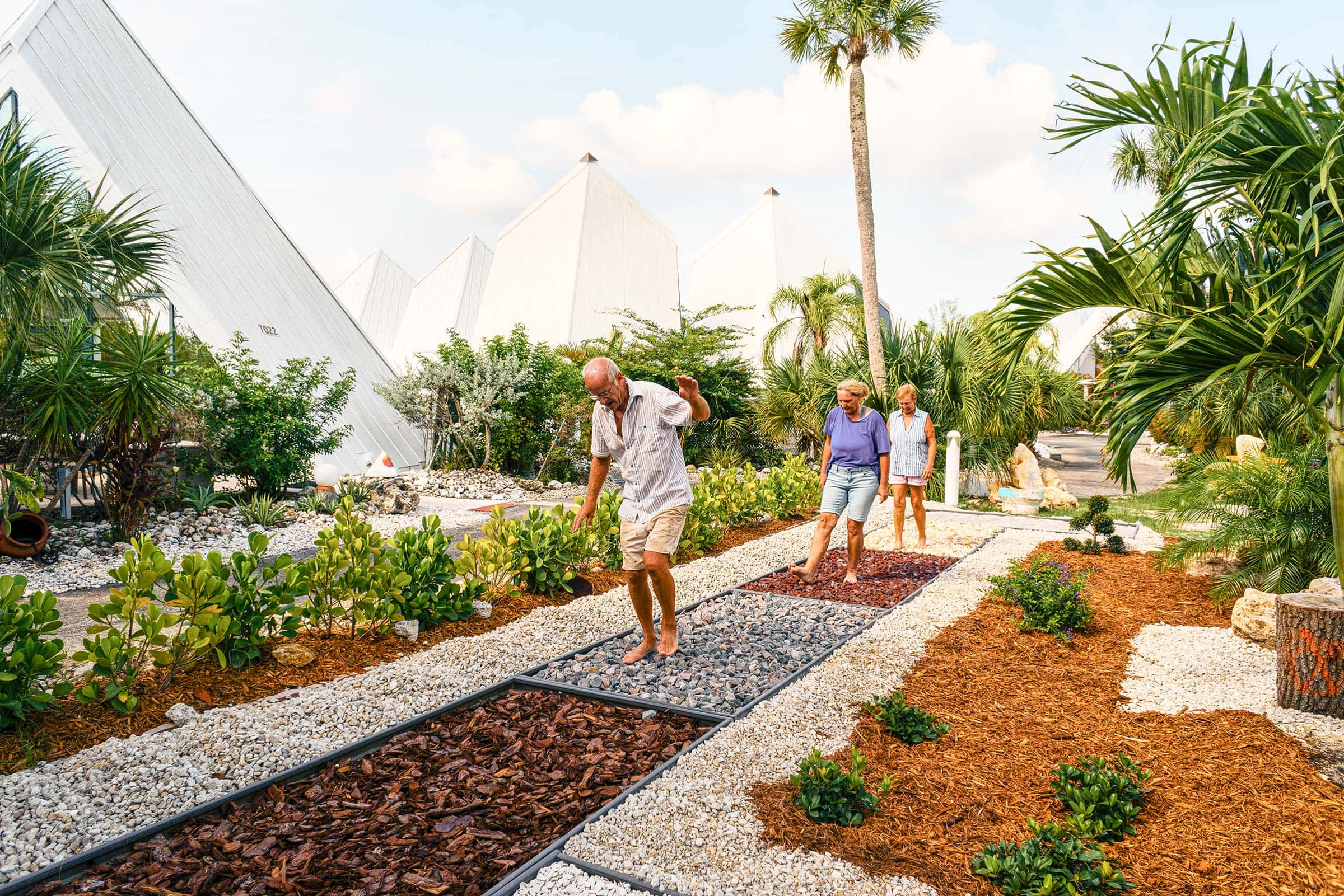 Three people walking along Pyramids in Florida's barefoot path which is constructed from different stones & wood textures