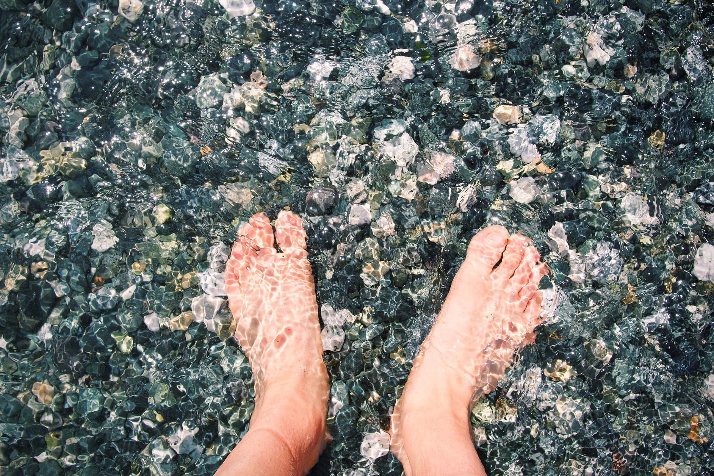 feet bathing in cold water filled with round stones
